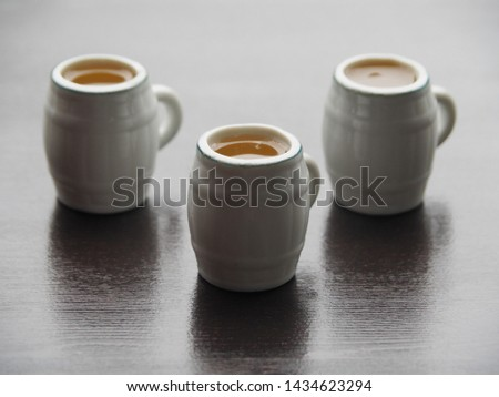 Three decorative beer mugs with light beer stand on a dark wooden table. Simple and original picture is with light beer mugs on a dark background.