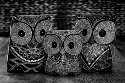 Three decorative painted owl ornaments rendered in monotone