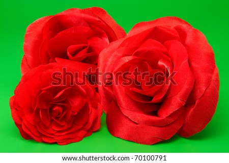 three decorative red silk roses on green background