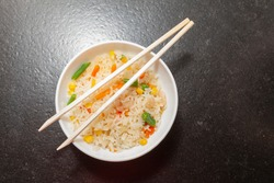 Three delicious Chinese rice with prawns, green beans, corn and carrots, served in a white bowl on which there are two chopsticks.