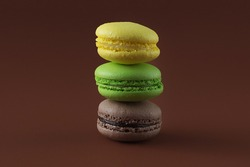 Three delicious fresh French macarons on a brown background. A stack of chocolate, apple and lemon brownies. Bright mouth-watering snacks. Horizontal photo, big plan