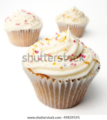 Three delicious freshly made homemade cupcakes isolated on a white background.