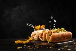 Three delicious hotdogs on dark wood background
