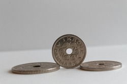Three Denmark coins lie on isolated white background Front coin Denomination is one krone (crown)