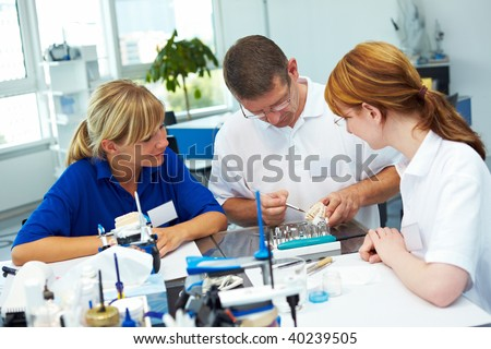 Three dental technicians working in a dental laboratory
