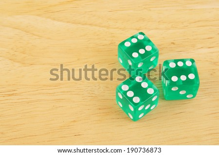 Three dices on wooden table with space for text