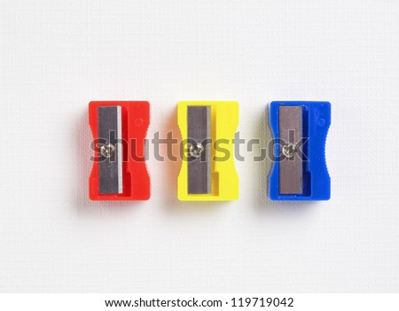 three different colors sharpener on white background