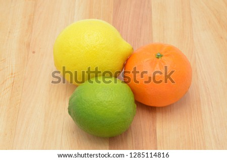Three different coloured fruits, orange, lime and a lemon. Fresh fruits are generally high in fiber, vitamin C, and water. Picture brings a feeling of a good and fresh morning.