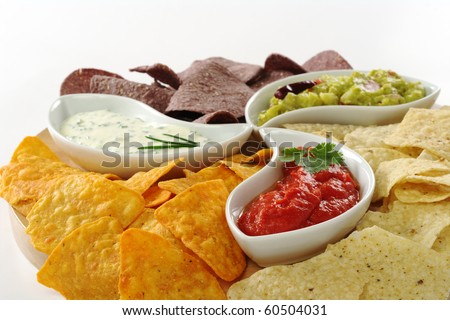 Three different dips (guacamole, tomato-chili and cream cheese dip) with salty and cheese tacos and chips made of Peruvian purple corn on white (Selective Focus)