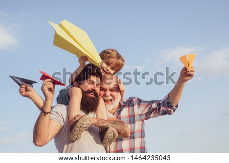 Three different generations ages: grandfather father and child son together. Father and son enjoying outdoor. Male multi generation family. Cute son with dad playing outdoor