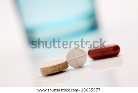 Three different medicine pills with glass of water
