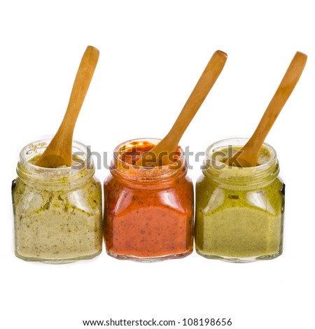 Three different sauces in glass jars with wooden spoons isolated on white background