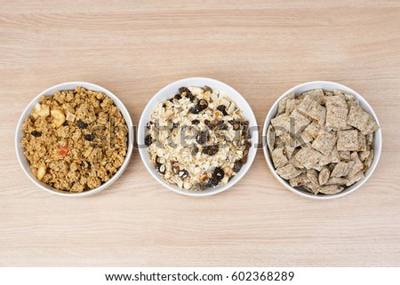 Three different types of Muesli in white bowls