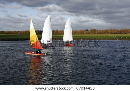 Three dinghy sailing boat on the river Thames at the countryside of Binsey, Oxford, England against a cold overcast cloudy sky.