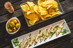 Three dishes with potato chips, picked anchovies and green olives on a dark wooden table with toothpicks. Typical Spanish snacks to eat in a bar.