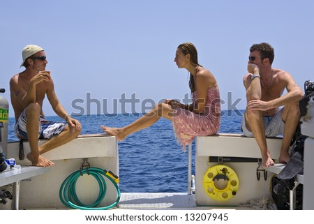 Three Divers relax on a Dive Boat during the Surface Interval
