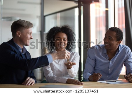 Three diverse people gathered in real estate agency, signing lease agreement afro woman receiving keys from first dwelling new home, realtor giving keys to female client after making a property deal