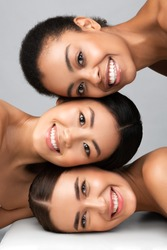 Three Diverse Women With Perfect Faces And Skin Posing Together Smiling To Camera On Gray Background. Multicultural Beauty Concept. Vertical