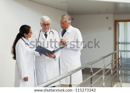 Three doctors talking in the corridor looking at patient files