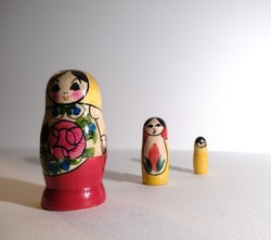 three dolls of different sizes are on the white background. matrushkas and babushkas. russian traditional dolls. empty  space for text. russia, moscow.