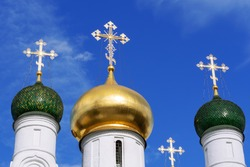 Three domes with crosses (one golden and two green) of the Orthodox Church, blue sky.