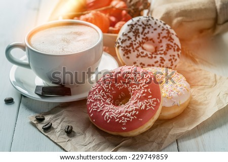 Three donut and a cup of coffee with chocolate on a white table