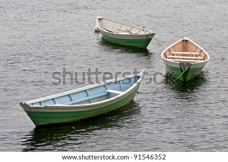three dory boats tethered in a row