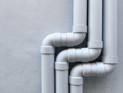 Three drain pipes on the gray wall