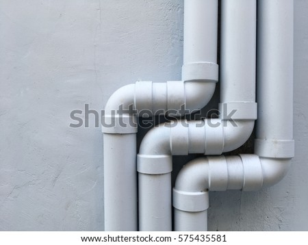 Three drain pipes on the gray wall