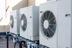 Three ductless mini-split air conditioners on a rooftop of a building