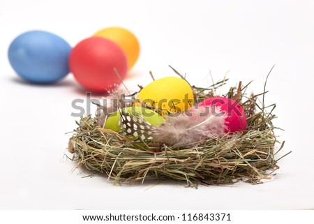 Three Easter eggs in a nest. In the background three other eggs on white