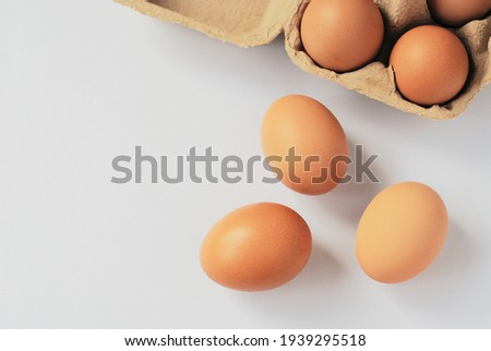 Three eggs out of egg tray isolated on white background. Eggs protected in brown recycle paper tray at ease of use and handle. Top view image with copy space.