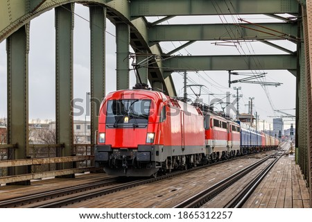 Three electric locomotives are pulling a very heavy and long freight train across a railway bridge. Winter weather. Austrian Railways Stock foto ©