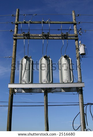 Three electrical power transformers installed on a platform and cabled in against a blue sky background