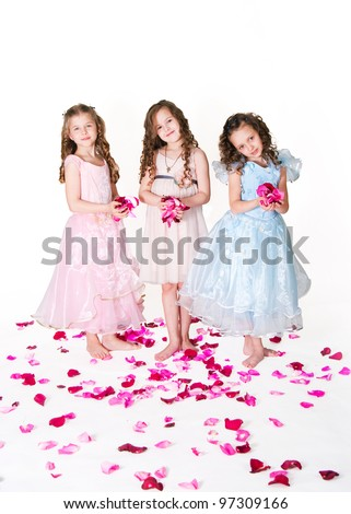 Three elegant girls on with rose-petals on a white background