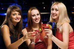 Three elegant ladies with cocktails at night club