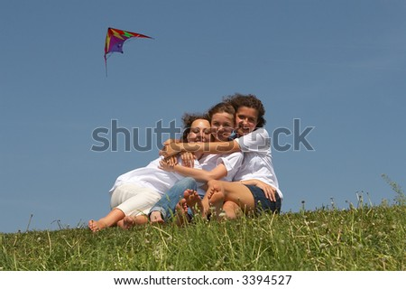 Three embracing girls on a green grass with a flying kite on a background