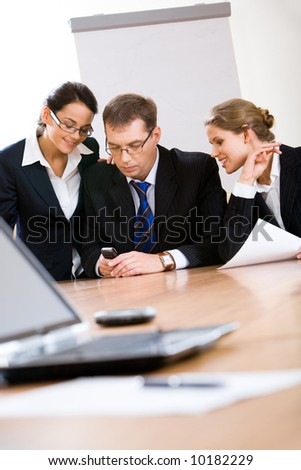 Three employees look at phone which the man holds at meeting