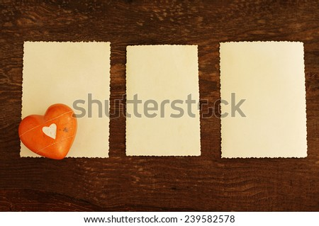 Three empty ancient photographs and heart on an old brown wooden background/ Three empty photographs and heart on an old wooden background