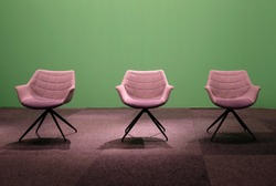 Three empty chairs in a studio with green screen