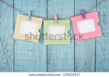 Three empty colorful photo frames or notes paper hanging with clothespins on wooden blue vintage shabby chic background