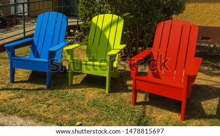 Three empty colourful wooden chairs sitting on the lawn, nobody in the image