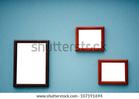 Three empty frame of picture on the blue wall