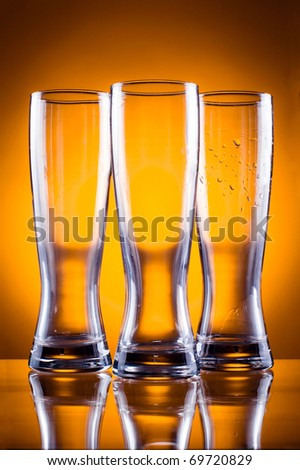 Three empty glass glasses for beer or drinks on a yellow background