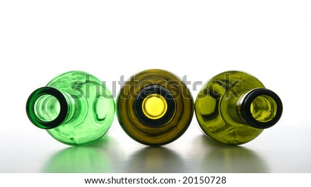 Three empty green wine bottles for recycling.