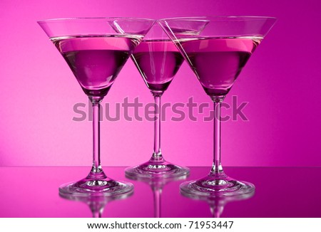 Three empty martini glasses on purple background