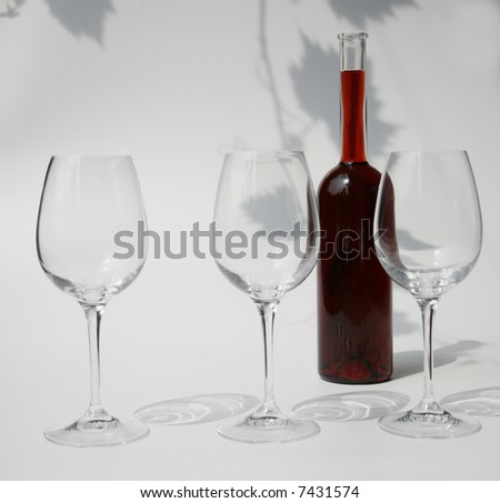 three empty wine glasses and a bottle filled with red wine against a background with the shadows of vine leaves