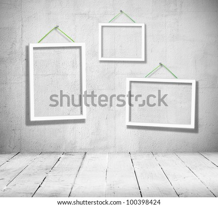 Three empty wooden frames for paintings hang in black and white vintage room on the wall. Template for design of the exhibition
