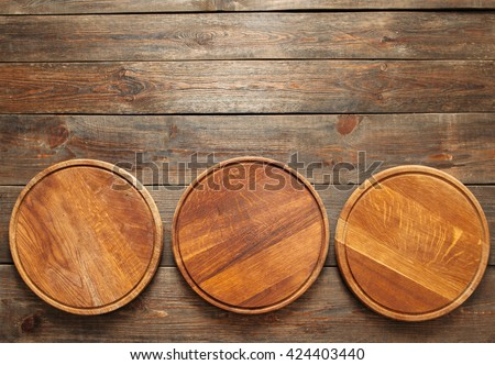 Three empty wooden pizza plates lie on the wooden table at the bottom of the picture. Copy space. Horizontal line. Flat lay of empty wooden pizza plates