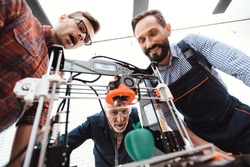 Three engineers are delighted to see how the 3d printer printed an apple model. They stand around the device and they are happy with the result.